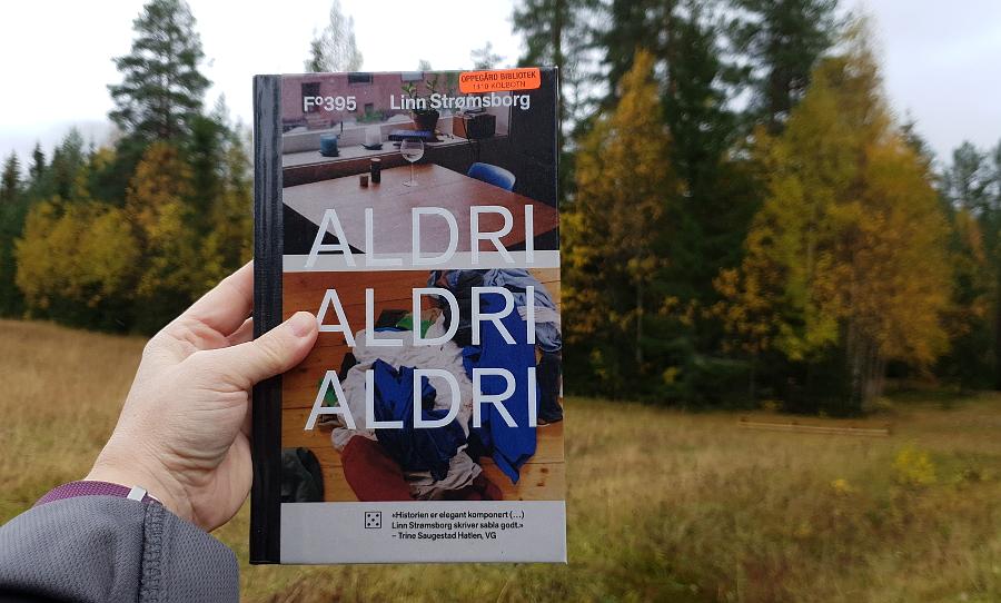 Hånd som holder boka Aldri, aldri, aldri av Linn Strømsborg. Bakgrunn er skog i høstfarger. Foto: Av en annen verden © 2019