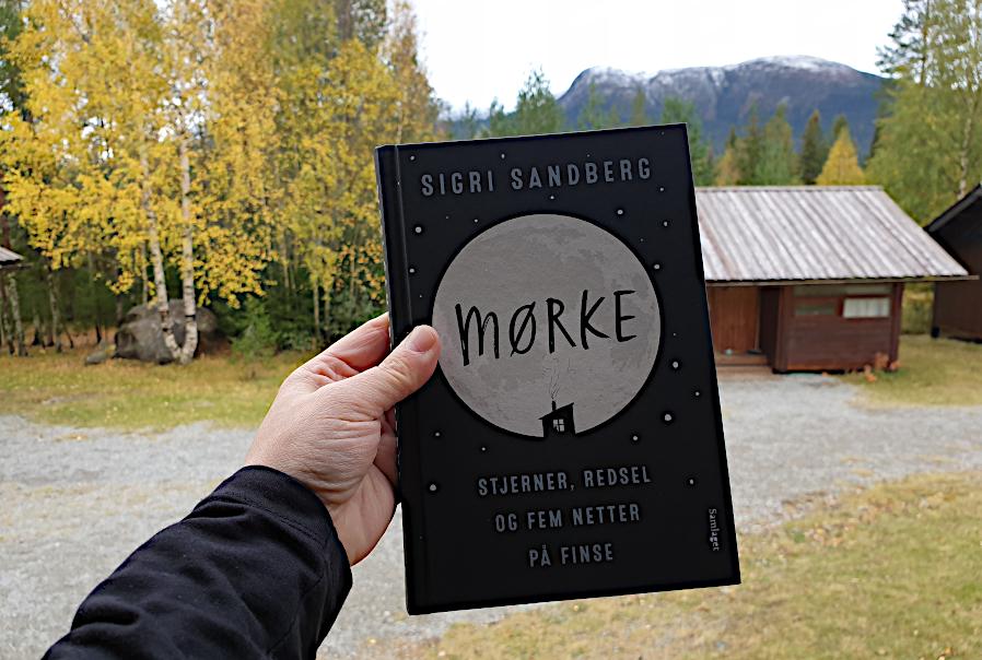 Bilde av boka Mørke av Sigri Sandberg foran hytte og en bakgrunn av fjell med snø og trær med høstfarger. Foto: Av en annen verden © 2019