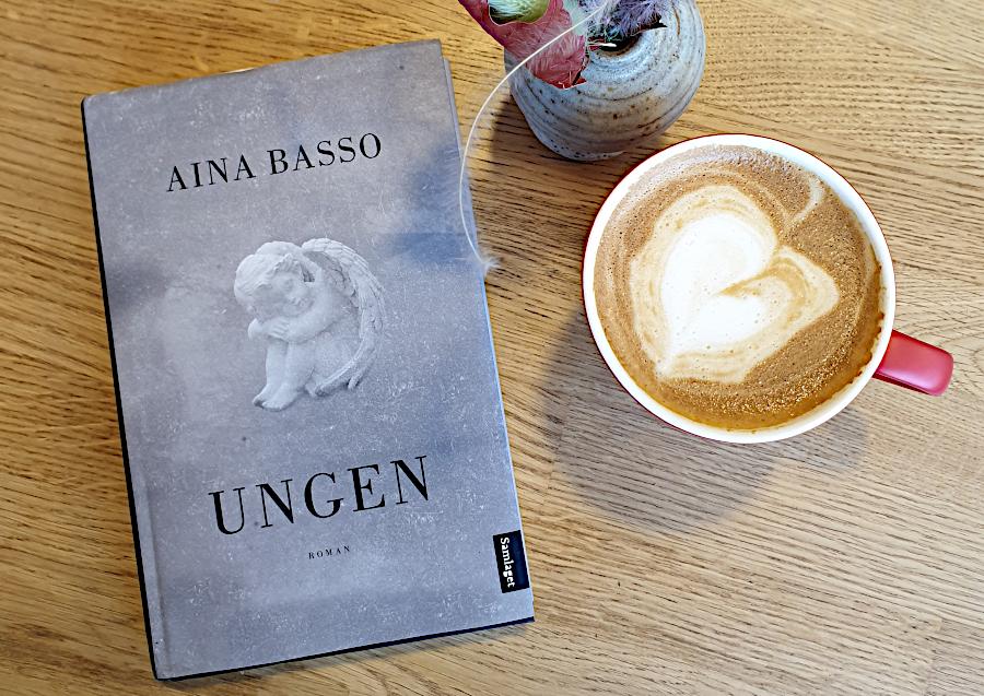 Bilde av boka Ungen av Aina Basso, sammen med en kopp kaffelatte av havremelk. Foto: Av en annen verden © 2019