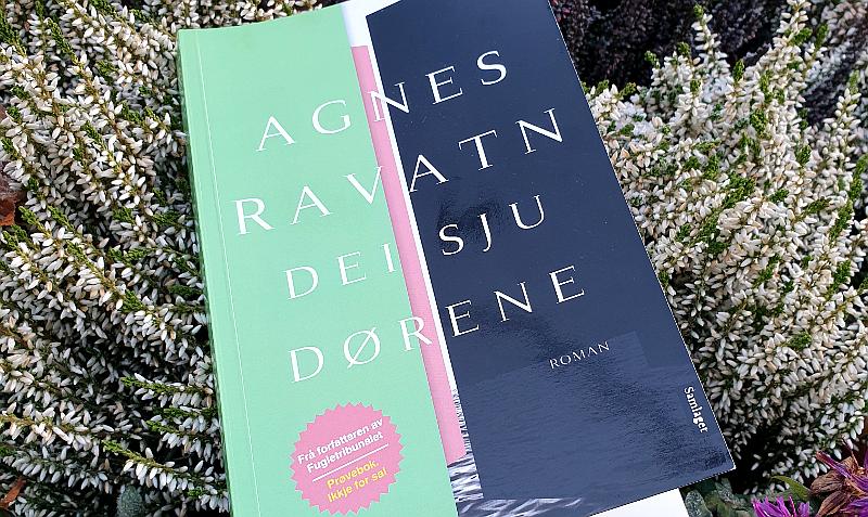 """Boka """"Dei sju dørene"""" av Agnes Ravatn i blomsterbed. Foto: Av en annen verden © 2019"""