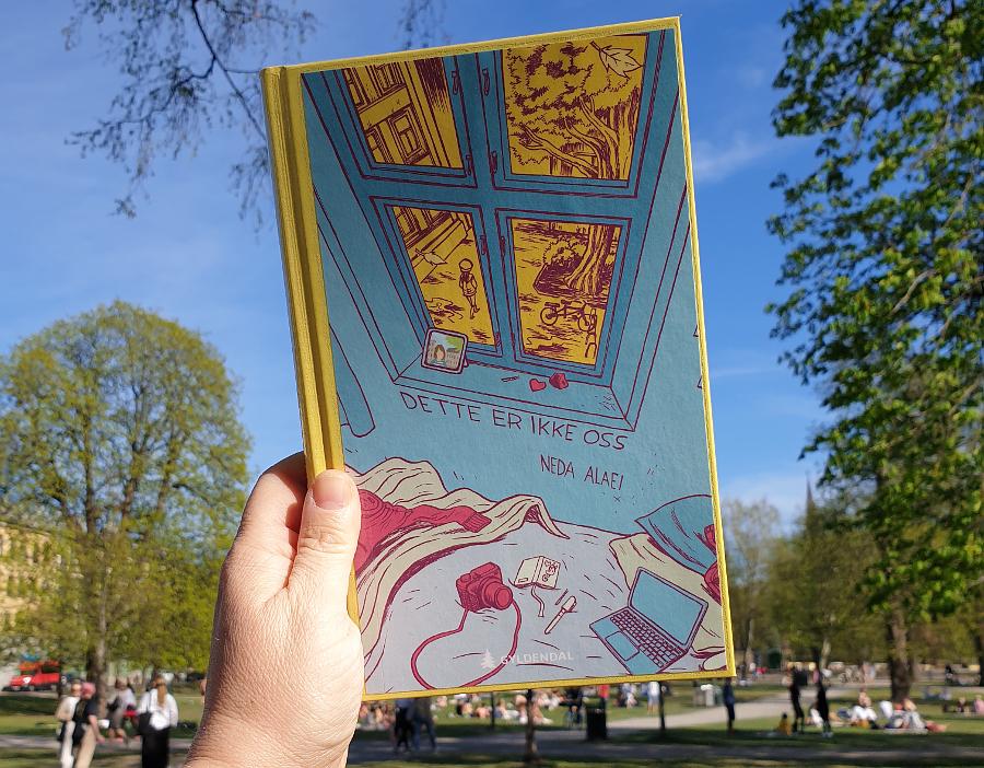 Boka Dette er ikke oss holder i ei hånd, med Sofienbergparken i Oslo som bakgrunn. Foto: Av en annen verden © 2020