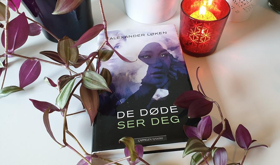 Boka De døde ser deg blant planter, og med en rød telysholde med tent lys i til høyre. Foto: Av en annen verden © 2020