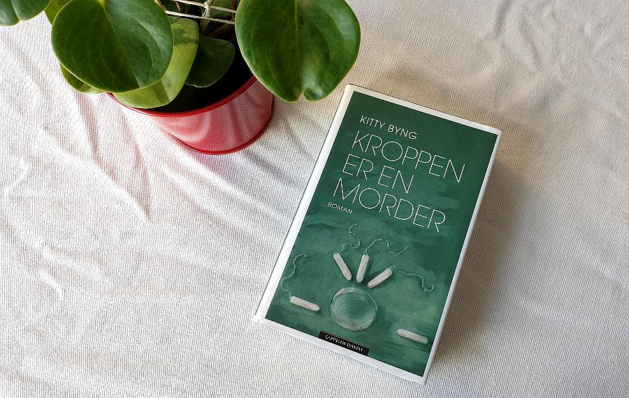 """Bilde av boka """"Kroppen er en morder"""" på en hvit duk. I hjørnet oppe til venstre er det en grønn plante i rød potteskjuler. Foto: Av en annen verden © 2020"""