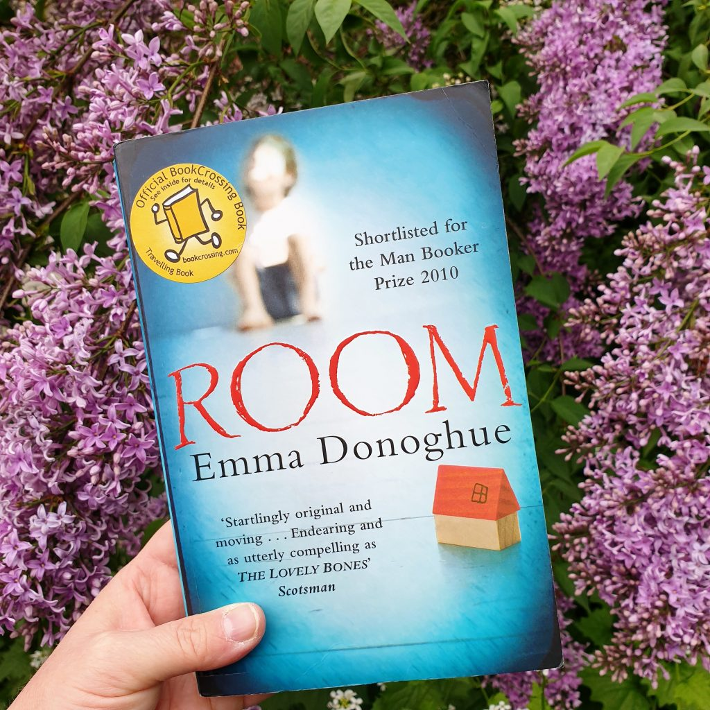 "Boka ""Room"" som holdes opp foran lilla syrin. Foto: Av en annen verden © 2020"