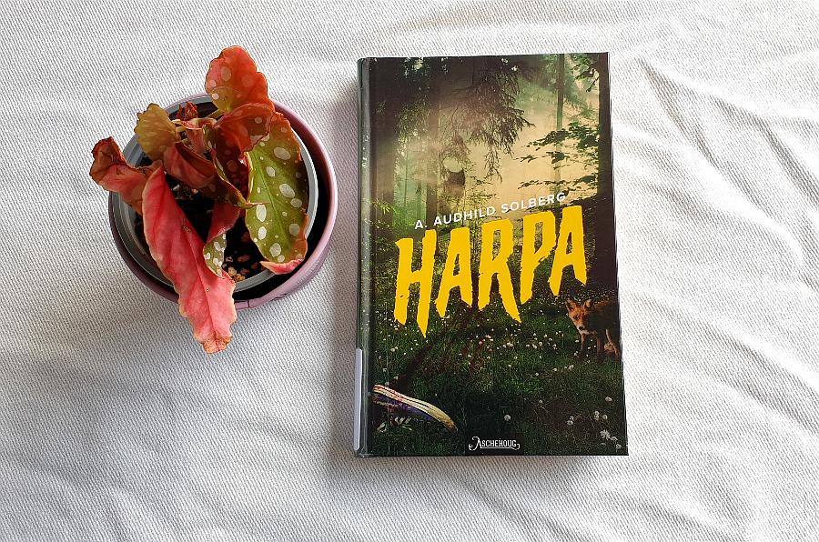 """Bilde av boka """"Harpa"""" som ligger på et bord med hvit duk. Til venstre for boka er det ei potteplante. Foto: Av en annen verden © 2020"""