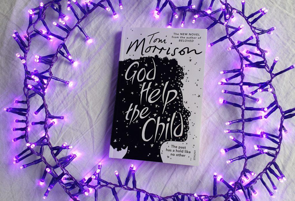 """Boka """"God help the child"""" av Toni Morrison ligger på hvitt underlag, omgitt av små, elektriske lys som er lilla. Foto: Av en annen verden © 2021"""