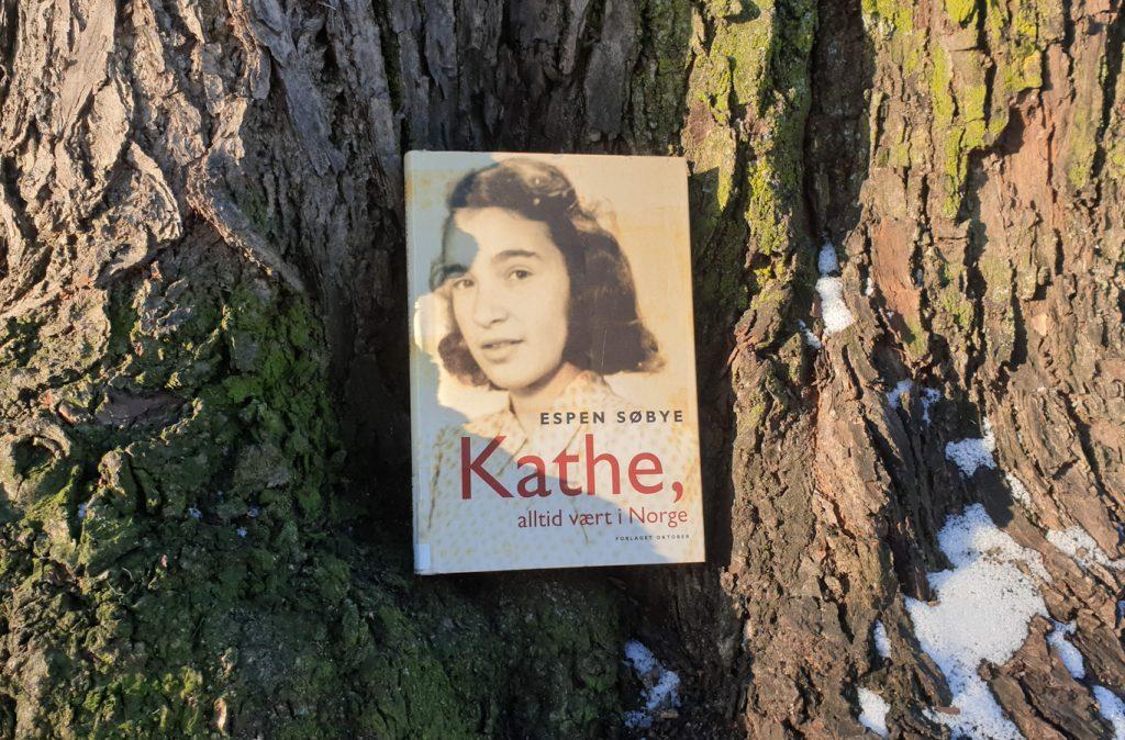 Bok står lent inntil en trestamme, som har litt snø på seg. Foto: Av en annen verden © 2021