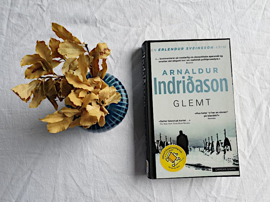 """Bilde av boka """"Glemt"""" ligger på et bord med hvit duk. Til venstre for boka er det en petroleumsblå vase med kvister i. Kvistene har tørkede blader i brun-/beigetoner. Foto: Av en annen verden © 2021"""