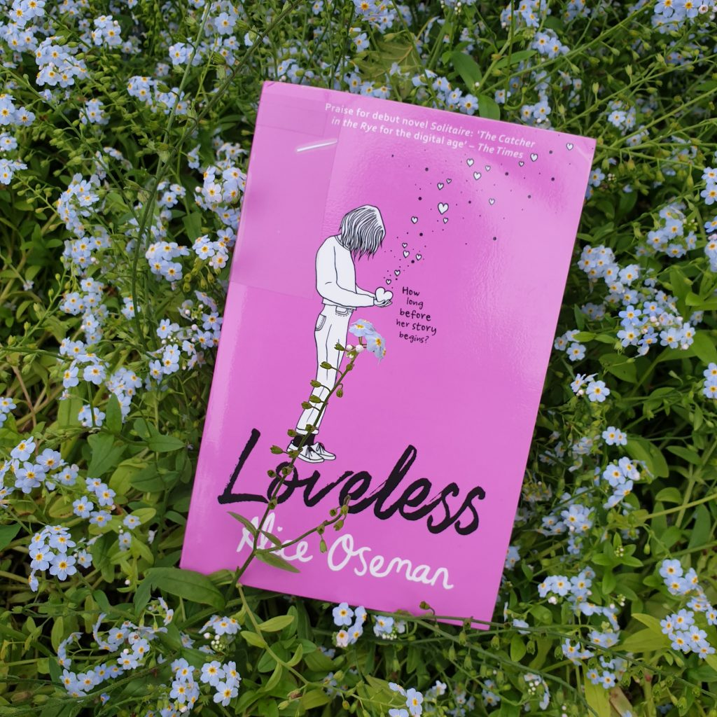 """Boka """"Loveless"""" av Alice Oseman ligger på en liten eng med forglemmegei-blomster. Foto: Av en annen verden © 2021"""