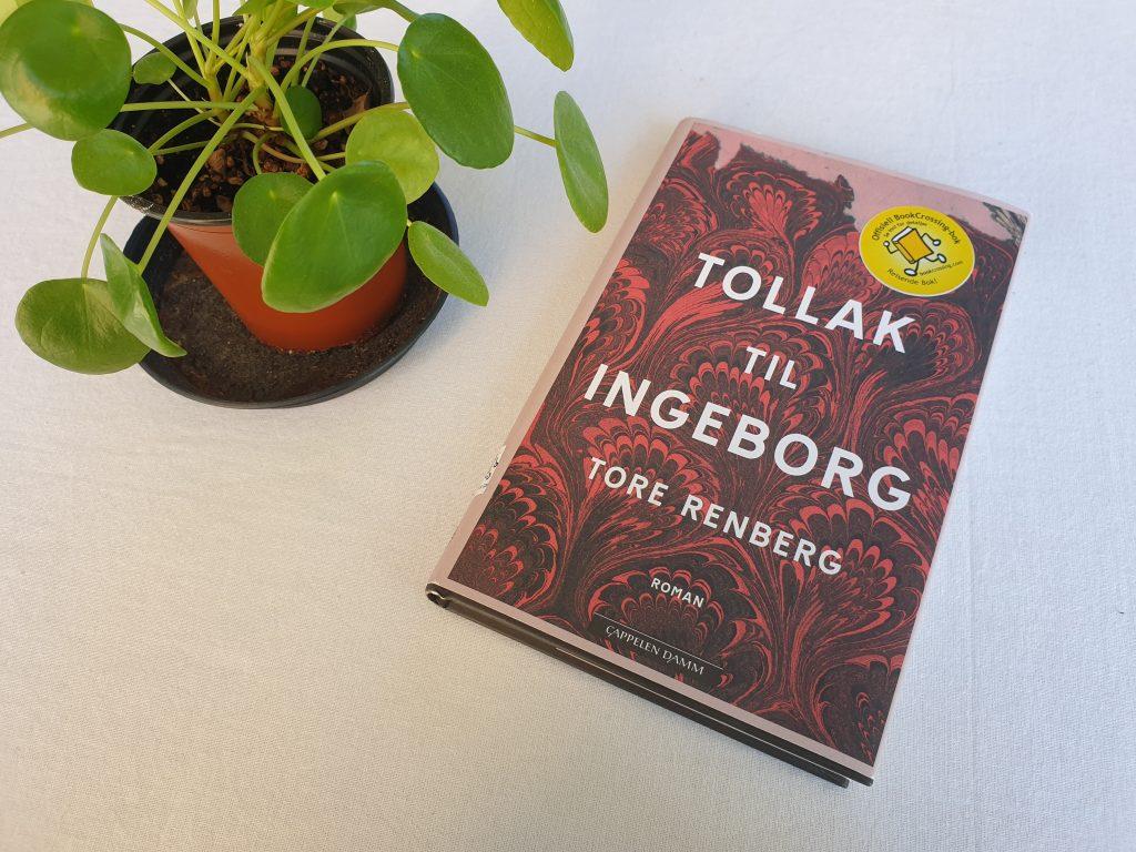 """Boka """"Tollak til Ingeborg"""" av Tore Renberg ligger på en bord med hvit duk. Til venstre for boka står en grønn plante. Foto: Av en annen verden © 2021"""